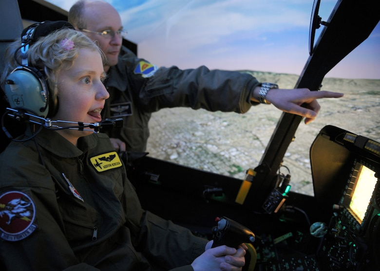 Addison Rerecich, a 13-year-old Tucsonan recovering from a double lung transplant, flies the A-10 Thunderbolt II simulator with help from U.S. Air Force Maj. Michael McKee, 358th Fighter Squadron pilot, during her tour of Davis-Monthan Air Force Base, Ariz. Feb. 21, 2013, as the Pilot for a Day participant. The D-M Pilot for a Day program invites children with serious or chronic conditions, to be a guest of the 355th Fighter Wing and one of the flying squadrons for an entire day. (U.S. Air Force photo by Senior Airman Brittany Dowdle)