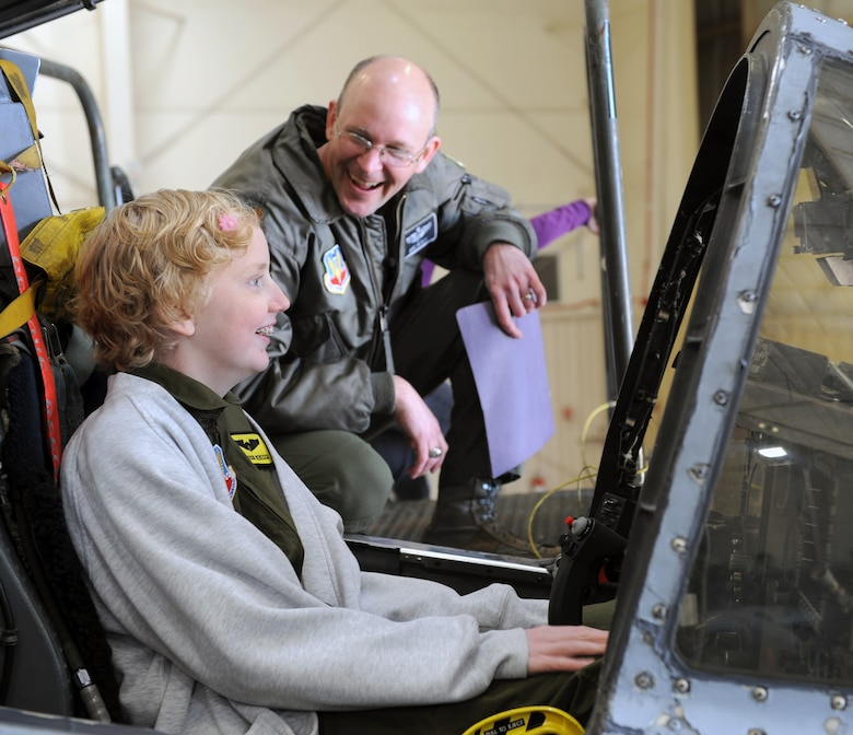 Addison Rerecich, a 13-year-old Tucsonan recovering from a double lung transplant, sits in the cockpit of an A-10 Thunderbolt II as U.S. Air Force Maj. Michael McKee, 358th Fighter Squadron pilot, shows her the details of the aircraft during her tour of Davis-Monthan Air Force Base, Ariz. Feb. 21, 2013, as part of the Pilot for a Day program. The goal of the Pilot for a Day program is to benefit children and their families in the local community who have catastrophic illnesses. (U.S. Air Force photo by Senior Airman Brittany Dowdle)