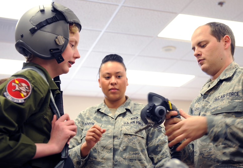 U.S. Air Force Staff Sgt. Daniel Hoover, 355th Operations Support Squadron air crew flight equipment technician, holds an oxygen mask, as he and Senior Airman Rachel Booth, 355th OSS air crew flight equipment technician, show Addison Rerecich, a 13-year-old recovering from a double lung transplant, how a pilot gears up for flight during her tour of Davis-Monthan Air Force Base, Ariz. Feb. 21, 2013, as part of the Pilot for a Day program. Each honorary pilot leaves with patches, souvenirs and memories to help sustain them in the face of their personal challenges. (U.S. Air Force photo by Senior Airman Brittany Dowdle)