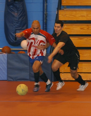 From left, Tech. Sgt. Javier Romero, 100th Force Support Squadron Fitness Center operations manager, tussles for the ball with Maj. Jose Zambrano, 95th Reconnaissance Squadron director of staff, during an indoor soccer match March 5, 2013, at the Northside Fitness Center, RAF Mildenhall, England. Romero scored two goals in the second half to give his team a narrow 3-2 win. (U.S. Air Force photo by Airman 1st Class Dillon Johnston/Released)