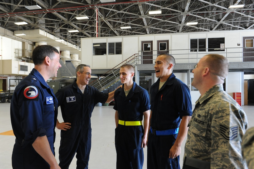 U.S. Air Force Brig. Gen. Matt Molloy, 18th Wing commander, and Chief Master Sgt. Ramon Colon-Lopez, 18th Wing command chief, interact with Airmen from the 18th Equipment Maintenance Squadron on Kadena Air Base, Japan, March 7, 2013. The Airmen briefed Kadena's leadership about the proper safety precautions they would need to take before working on a U.S. Air Force F-15 Eagle fighter aircraft. (U.S. Air Force photo/Airman 1st Class Malia Jenkins)