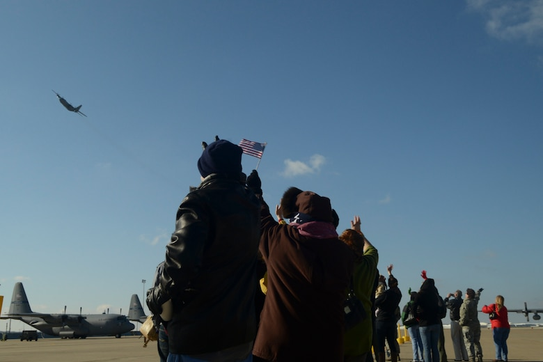 Friends and family of the 136th Airlift Wing wave at the C-130 aircraft as it flies by prior to departing for Southwest Asia at NAS Fort Worth JRB, Texas, Feb. 26, 2013. The Airmen will support the Air Expeditionary Forces in Southwest Asia from 60 to 180 days.. (National Guard photos by Senior Master Sgt. Elizabeth Gilbert)
