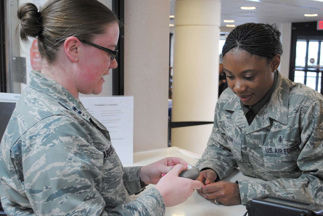 """Capt. Julie Carpenter, 341st Medical Group pharmacist, left, shows Tech. Sgt. Shontell Nelson, 341st Medical Support Squadron flight chief, the proper way to use an inhaler.  Carpenter's job, as well as the other pharmacy members, consists mainly of """"behind-the-scenes"""" work, which she doesn't mind because she says all work helps the entire Biomedical Services Corps develop one single voice.  (U.S. Air Force photo/Senior Airman Cortney Paxton)"""
