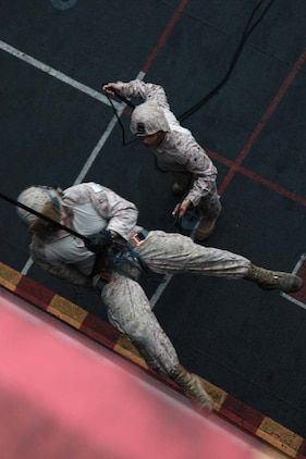 A Marine with the 15th Marine Expeditionary Unit rappels off the flight deck of USS Peleliu, March 5.  The main training objective was keeping the 14 BLT Helicopter Rope Suspension Technique masters current in their qualifications, but it also gave the Security Platoon an opportunity to practice rappelling, which is one of the ways troops can be inserted into different situations.  The 15th MEU is deployed as part of the Peleliu Amphibious Ready Group as a U.S. Central Command theater reserve force, providing support for maritime security operations and theater security cooperation efforts in the U.S. 5th Fleet area of responsibility. (U.S. Marine Corps photo by Cpl. John Robbart III)