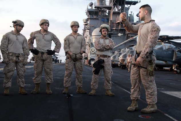 Sergeant Scott W. Gilchrist, recovery team leader, 81mm Mortars/Tactical Recovery of Aircraft and Personnel Platoon, Weapons Company, Battalion Landing Team 3/5, 15th Marine Expeditionary Unit, explains rappelling techniques to Marines during training off the flight deck of the USS Peleliu, March 5.  The main training objective was keeping the 14 BLT Helicopter Rope Suspension Technique masters current in their qualifications, but it also gave the Security Platoon an opportunity to practice rappelling, which is one of the ways troops can be inserted into different situations. The 15th MEU is deployed as part of the Peleliu Amphibious Ready Group as a U.S. Central Command theater reserve force, providing support for maritime security operations and theater security cooperation efforts in the U.S. 5th Fleet area of responsibility. Gilchrist, 24, is from Hurst, Texas, and is a HRST master with the unit. (U.S. Marine Corps photo by Cpl. John Robbart III)