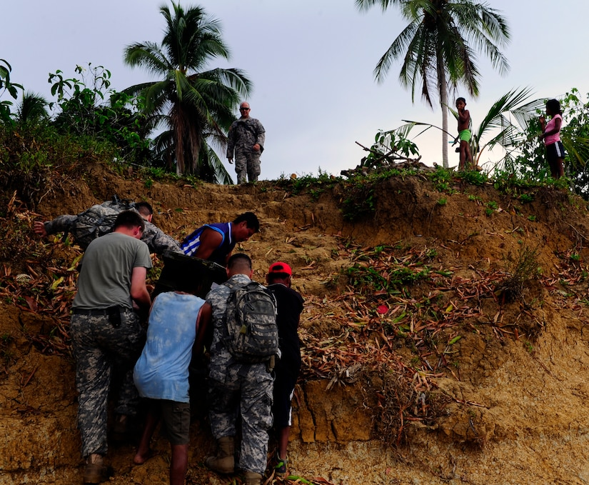 Joint Task Force-Bravo personnel get help from village residents to transport medical supplies to the site of a Medical Readiness Training Exercise in Marraganti, Panama March 1, 2013. Joint Task Force-Bravo partnered with the Panama Ministry of Health, Panama Ministry of Education and Servicio Nacional de Fronteras to exercise their expeditionary medical and mission command capabilities in preparation for future disaster relief events. (U.S. Air Force photo by Capt. Rebecca Heyse)