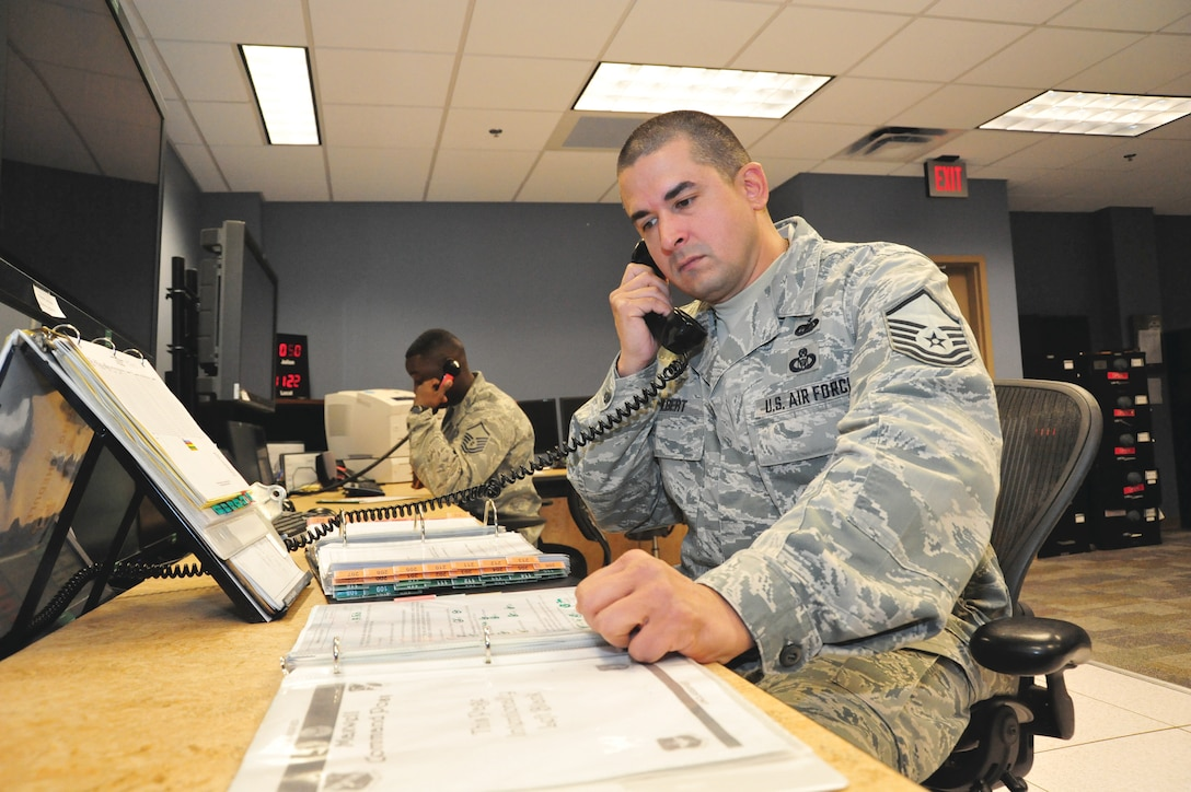 Master Sgt. Lamar Colbert, senior Air Reserve technician for the Maxwell command post, reviews a checklist used to respond to base emergencies here Feb. 19. Since the Maxwell command post combined in 2011, reservists work alongside active-duty Airmen to better facilitate 42nd Air Base Wing and 908th Airlift Wing missions. The 42nd ABW is the host organization for the base, while the Airmen of the 908th AW operate the seven C-130H Hercules stationed at Maxwell. (U.S. Air Force photo by Staff Sgt. Sandra Percival)