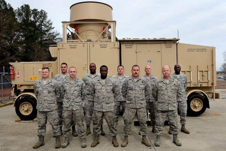 Members of the 245th Air Traffic Control Squadron at McEntire Joint National Guard Base, S.C., pose for a photo in front of a mobile Tactical Air Navigation unit, Feb. 14, 2013. The group was awarded the Airfield Operations Flight complex of the year.(National Guard photo by Tech. Sgt. Caycee Watson/Released)