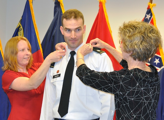 U.S. Army Corps of Engineers Nashville District Deputy District Commander Lt. Col. Patrick Dagon, (center) from Butler, Ill., gets his shoulder boards placed on by his wife, Emily (left) and his mother, Myra (right) during a promotion ceremony March 8, 2013, at the U.S. Army Corps of Engineers Nashville District Headquarters, in Nashville, Tenn. Dagon has been with the Nashville District since Aug 2011. His next assignment is with the Defense Threat Reduction Agency at Kirtland Air Force Base, Albuquerque, N.M., with a report date in August. (USACE photo by Mark Rankin)
