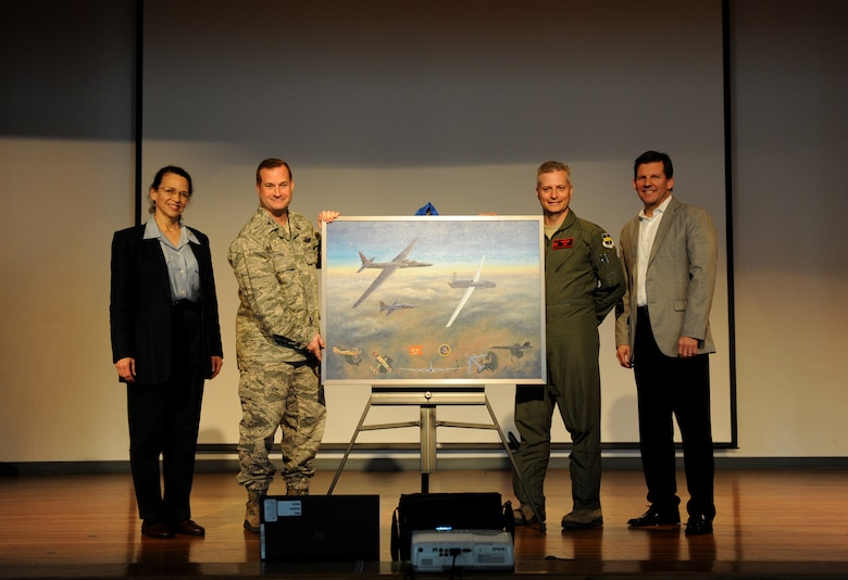 """Aviation artist Kristin Hill (left) and Dave Schmall (right) present Col. Phil Stewart, 9th Reconnaissance Wing commander and Lt. Col. Stephen Rodriguez, 1st Reconnaissance Squadron commander with a painting depicting the centennial of the 1st RS at Beale Air Force Base, Calif., March 7, 2013. The painting features many aircraft flown by the 1st RS including the U-2 """"Dragon Lady"""" and SR-71 Black Bird. (U.S. Air Force photo by Staff Sgt. Robert M. Trujillo/Released)"""