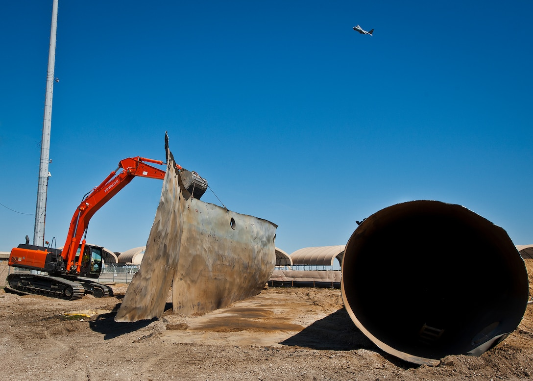 An excavator picks up a flattened piece of a 50,000 gallon underground fuel storage tank as a C-130 flies overhead near the 33rd Fighter Wing March 11 at Eglin Air Force Base, Fla.  The tank was one of four removed from the area.  The systems have been in place since 1959 and formerly used to refuel 33rd FW aircraft until recently.  The new fuel storage system is already in place and increases the wing's capacity to more than a million gallons of JP-8 for the F-35s.  (U.S. Air Force photo/Samuel King Jr.)