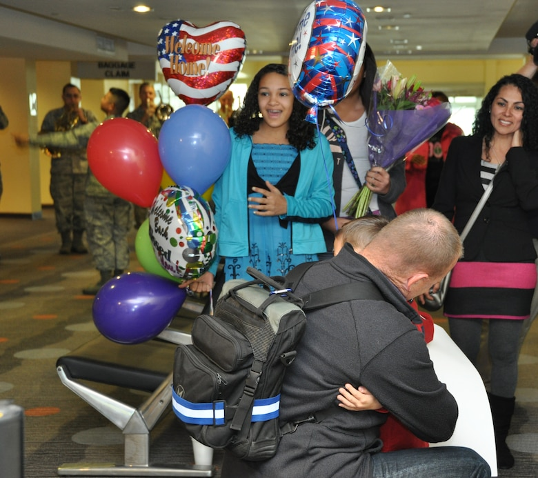 Tech Sgt. Steven Moore, an audio technician with the Band of the U.S. Air Force Reserve, embaces his son Matthew during the welcome home celebration at the Macon Regional Airport, March 8. Moore and five other members of the band completed a nearly 4-month deployment to Southwest Asia. Their return signaled the final overseas deployment for the band, which is slated for deactivation at the end of September 2013. (U.S. Air Force photo/Philip Rhodes)