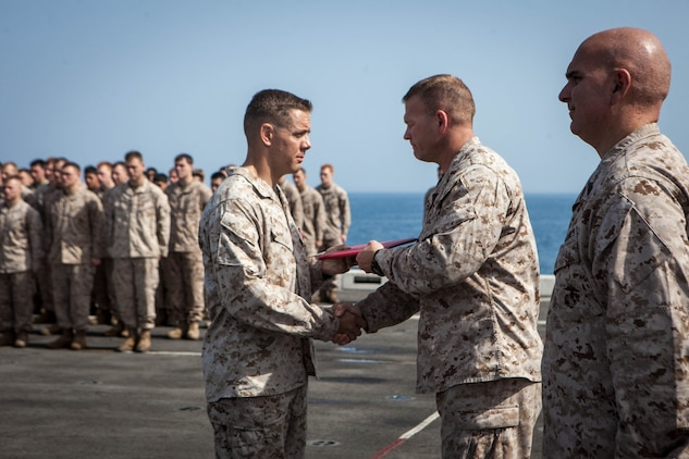 Major Matthew Peterson, operations officer,  Battalion Landing Team 3/5, 15th Marine Expeditionary Unit,  receives the citation for his Bronze Star Medal from Lt. Col. Christeon Griffith, his battalion commander, aboard USS Green Bay, March 3. Peterson received the award for his extraordinary guidance, zealous initiative and total dedication to duty while securing the historically violent and enemy controlled urban area of Wishtan and the surrounding region. The 15th MEU is deployed as part of the Peleliu Amphibious Ready Group as a U.S. Central Command theatre reserve force, providing support for maritime security operations and theatre security cooperation efforts in the U.S. 5th Fleet area of responsibility. (U.S. Marine Corps photo by Cpl. Bobby J. Gonzalez/Released)