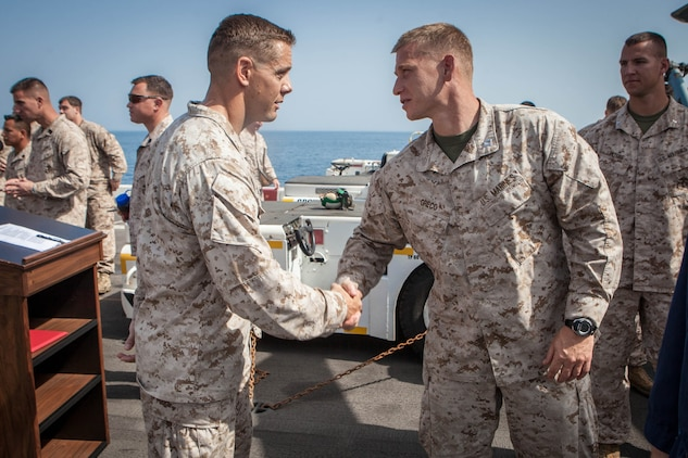 Captain Jerome Greco (right), commanding officer, Lima Company, Battalion Landing Team 3/5, 15th Marine Expeditionary Unit, congratulates Maj. Matthew Peterson, operations officer, BLT 3/5,  after his Bronze Star award ceremony aboard USS Green Bay, March 3. Peterson received the award for his extraordinary guidance, zealous initiative and total dedication to duty while securing the historically violent and enemy controlled urban area of Wishtan and the surrounding region. The 15th MEU is deployed as part of the Peleliu Amphibious Ready Group as a U.S. Central Command theatre reserve force, providing support for maritime security operations and theatre security cooperation efforts in the U.S. 5th Fleet area of responsibility. (U.S. Marine Corps photo by Cpl. Bobby J. Gonzalez/Released)