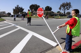 Jordan Pendexter, a 10-year-old student of North Terrace Elementary School, and a faculty supervisor hold traffic to help students cross the street, Mar. 12. As the faculty supervisor blows the whistle, Pendexter lowers the stop sign to signal the oncoming traffic.
