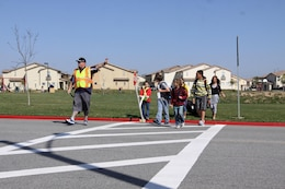 Jordan Pendexter, a 10-year-old student of North Terrace Elementary School, lowers a stop sign to cease oncoming traffic and allow his fellow students to use the crosswalk outside the school March 12.
