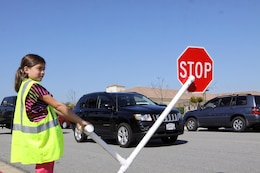 Julie Riley, a 10-year-old student attending North Terrace Elementary School, holds the stop sign out to halt traffic and allow pedestrians to cross March 12. Julie and three other students volunteered to help make the crosswalk safer for both vehicles and pedestrians.