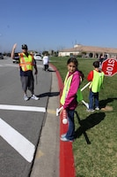 """Christina Candia, a 10-year-old fifth grader of North Terrace Elementary School, holds the """"candy cane"""" pole to prevent students from running across the street before the traffic was stopped. The supervising faculty used whistles and hand gestures to signal traffic in the intersection."""