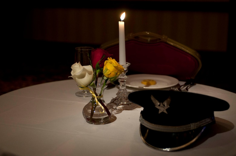 Commonplace among military functions is the Missing In Action/Prisoner of War table. The vase that holds the red, white and yellow roses represent those killed in action, those who have returned and those who are missing, respectively. The white table cloth underneath symbolizes the purity of an American service member's intentions when responding to their country's call to arms. The Missing in Action/Prisoner of War table was prominently set at the front of the banquet room for the 2013 Outstanding Airman of the Year Banquet (OAY) held March 9 at the JW Marriott Tucson Starr Pass Resort and Spa. (Air National Guard photo by Tech. Sgt. Hollie Hansen)