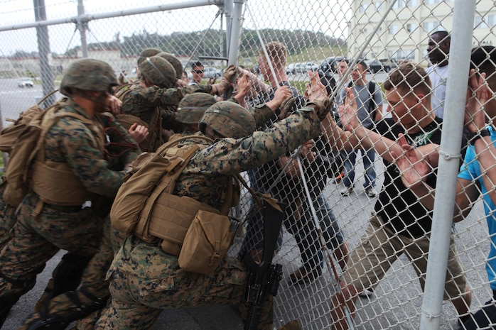 Marines with Fox Battery, Battalion Landing Team 1st Battalion, 5th Marines, 31st Marine Expeditionary Unit, acting as the quick reaction force of the 31st MEU's Forward Command Element, attempt to push through the gate of the notional U.S. Embassy to quell hostile protesters here, March 11. The FCE is the 31st MEU's on-site survey and planning cell when responding to a request for humanitarian assistance or disaster relief aid in a foreign country. The 31st MEU is currently conducting its semiannual Certification Exercise, where the unit's full range of capabilities are evaluated by the Special Operations Training Group, III Marine Expeditionary Force, with the purpose of maintaining the MEU's proficiency. The 31st MEU is the only continuously forward-deployed MEU and is the Marine Corps' force in readiness in the Asia-Pacific region.