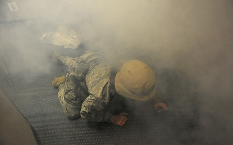 A U. S. Air Force Airman from the 366th Communications Squadron crawls low to the ground to get out of a building with a simulated fire, March 6, 2013, at Mountain Home Air Force Base, Idaho. An Operational Readiness Exercise has been held each month to test the knowledge of procedures. (U.S. Air Force photo/Senior Airman Heather Hayward)