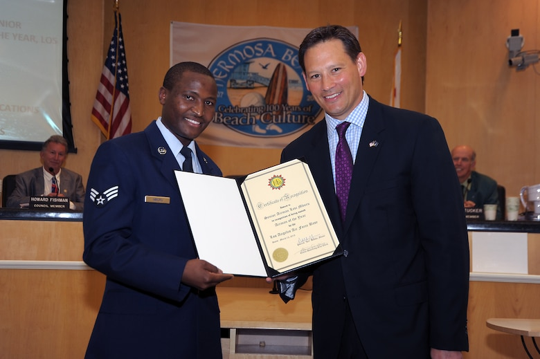 Senior Airman Levi Mburu (left) receives a certificate of recognition from Hermosa Beach Mayor, Patrick Bobko, during a council meeting Mar 12, 2013. SrA Mburu was selected as the Airman of the Year for Los Angeles Air Force Base, home of the Space and Missile Systems Center in El Segundo, Calif.