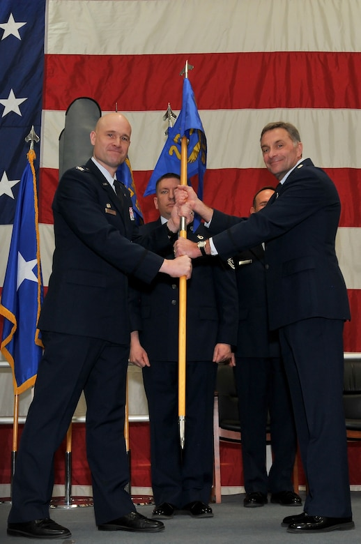 Air National Guard Col. Gregory T. White, 233d Space Group Commander, hands the 233d Space Communications Squadron flag to Lt. Col. Thomas D. Book, the newly appointed 233d Space Communications Squadron Commander, during the 233d Space Group Activation Ceremony, March 10, 2013, Greeley Air National Guard Station, Greeley, Colo. The 137th Space Warning Squadron reorganized as the 233d Space Group and will continue to operate under the 140th Wing, performing the one-of-a-kind Mobile Ground System mission that these men and women have been doing since 1996. (Air National Guard photo by Tech. Sgt. Wolfram M. Stumpf)