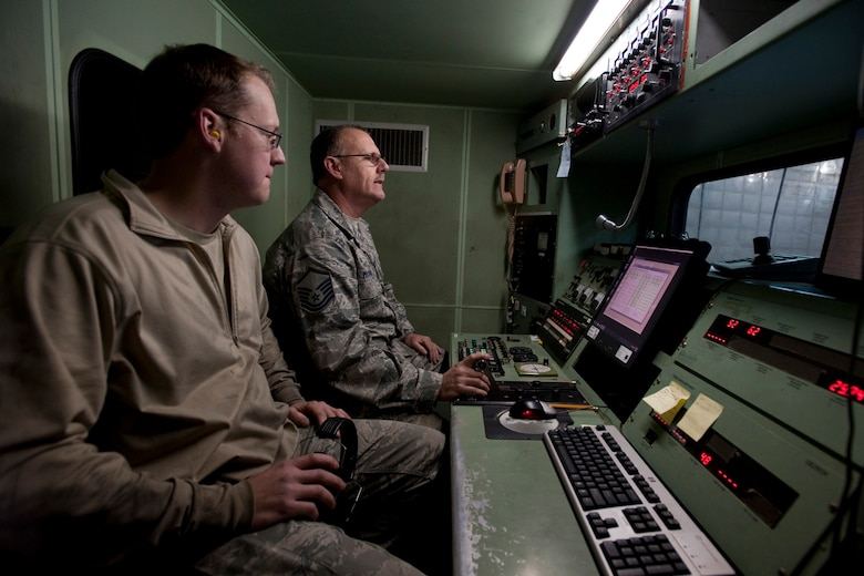 U.S. Air Force Airman 1st Class Jonathan Salvador watches as Master Sgt. Rick Morgan, a mechanic with the 169th Maintenance Squadron propulsion unit at McEntire Joint National Guard Base, S.C., controls the block 52 jet engine and observes instrument readings from inside the T-20 test cab at the hush house, March 2, 2013. Salvador and Morgan are inspecting the engine for leaks in case the engine is faulty it will need a complete overhaul. The hush house allows jet engine mechanics to test F-16 engines without having extra noise pollution disturb base operations. (National Guard photo by Staff Sgt. Jorge Intriago/Released)