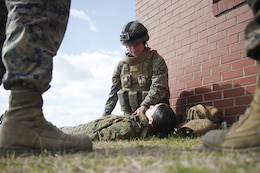 Cpl. Stephanie Abelino, a Marine Aircraft Group 14 warehouse clerk, checks the vitals on a victim with a simulated injury during a combat lifesaver course conducted aboard Marine Corps Auxiliary Landing Field Bogue March 6.