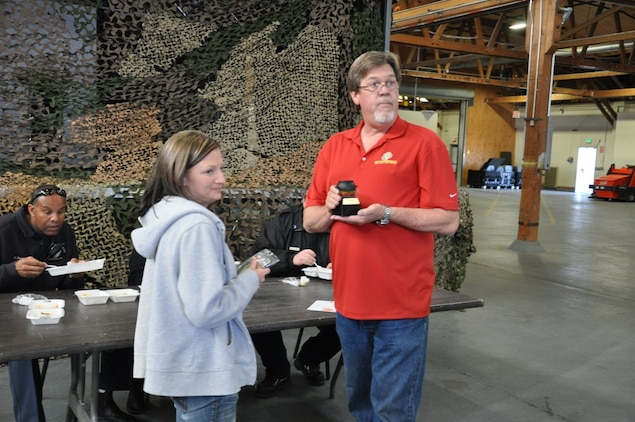 Stacey Decker, a supply technician with Fleet Support Division on Marine Corps Logistics Base Barstow, Yermo Annex, receives a trophy from Gregory Johnson, FSD's chili cook-off committee chairman, for winning the 2nd annual chili cook-off challenge, March 6. The friendly competition raises money for FSD's employee appreciation day.