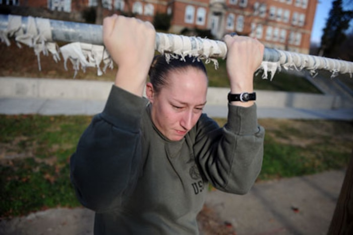 Sgt. Stephany Rector, administrative specialist, installation personnel administration center, Headquarters Company, Headquarters and Service Battalion, completes pull-ups outside of her office, Dec. 3. Starting Jan. 1, 2014, female Marines, poolees, and officer candidates will perform dead-hang pull-ups rather than the flexed arm-hang during their physical fitness tests.