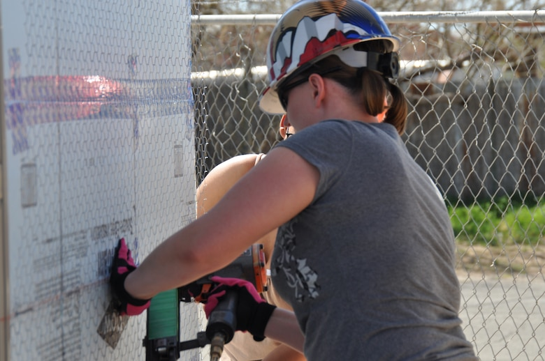 Master Sgt. Nicole Langdon, 612th Air and Space Operation Center, nails outdoor stucco preparation paper to an exterior wall on a Habitat for Humanity home in Tucson, Ariz., March 14. More than 45 Airmen from Davis-Monthan AFB came together to donate six hours of their off-duty time to build homes in support of the local community. (USAF photo by Master Sgt. Kelly Ogden/Released).