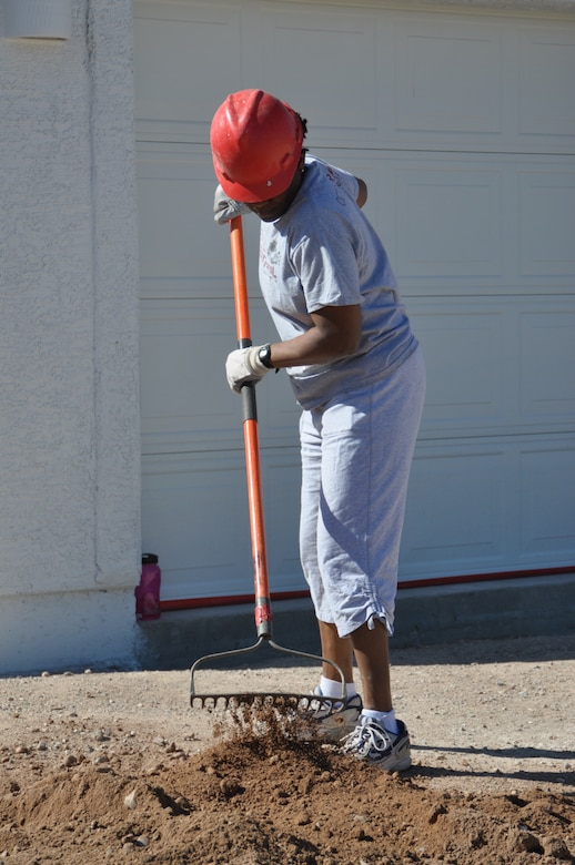 Maj. Jennifer Johnson, 612th Air and Space Operations Center, preps a Habitat for Humanity home for landscaping in Tucson, Ariz., March 14. More than 45 Airmen from Davis-Monthan AFB came together to donate six hours of their off-duty time to build homes in support of the local community.  (USAF photo by Master Sgt. Kelly Ogden/Released).