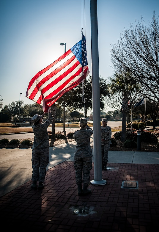 Senior Airman Danielle Redman, 628th Comptrollers Squadron finance specialist, secures the flag as it is guided down during a Women's History Month Retreat March 8, 2013, at Joint Base Charleston – Air Base, S.C. Redman and several other Airmen from JB Charleston participated in the ceremony. (U.S. Air Force photo/ Senior Airman Dennis Sloan)