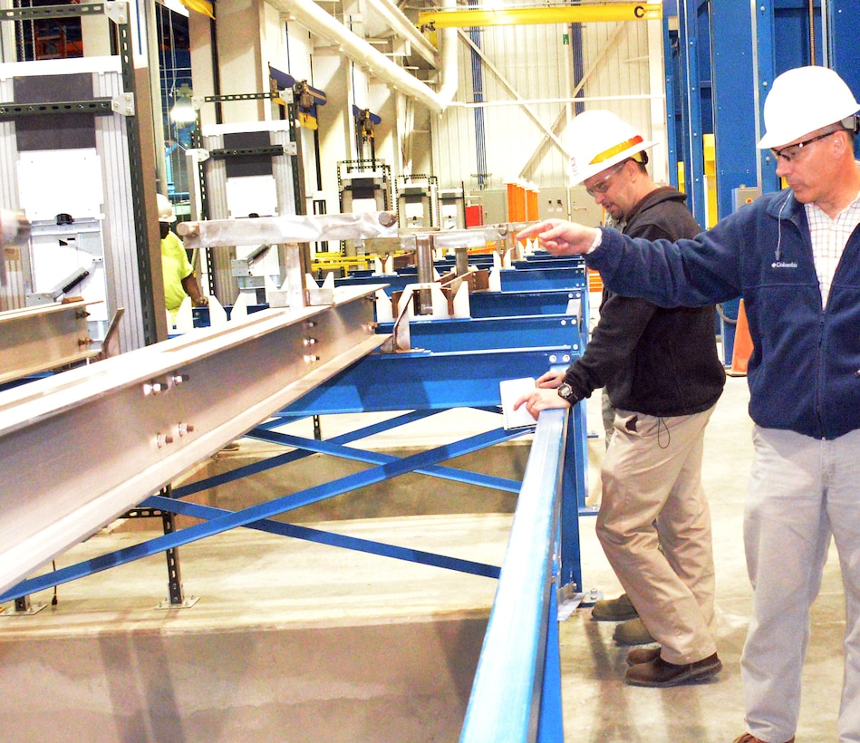 Front, Jim Cunningham, 402nd Commodities Maintenance Support Squadron process engineer, and Harold Livingston, U.S. Army Corps of Engineers Advanced Metal Finishing Facility Quality Assurance Examiner, stand in the staging area where aircraft parts will be prepped before being loaded onto an assembly line for 'wet' processing. U. S. Air Force photo/Ed Aspera)