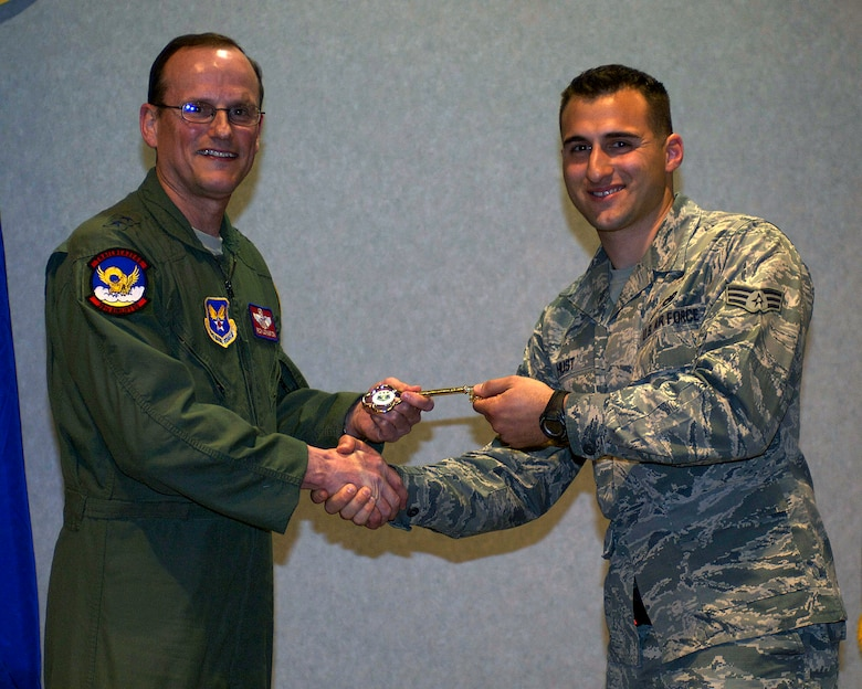 U.S. Air Force Maj. Gen. Richard C. Johnston, assistant deputy under secretary of the Air Force, international affairs, left, presents Senior Airman Jeremiah Hust, 317th Airlift Group, with the honorary key to the newest C-130J March 12, 2013, at Dyess Air Force Base, Texas. Dyess has received 26 of 28 J-Models and expects the next to be delivered in June. (U.S. Air Force photo by Airman 1st Class Kylsee Wisseman/ Released)