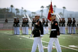 Capt. Christopher Hall, the Drum and Bugle Corps executive officer and Lance Cpl. Tyler Thompson, the Battle Color Detachment guidon bearer, march on to the field during the Battle Color Ceremony at the Paige Fieldhouse Football Field here March 15.