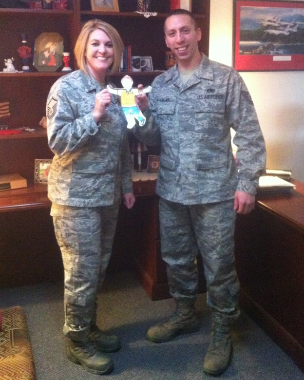 U.S. Air Force Master Sgt. Karren Gantt, 366th Fighter Wing career assistant advisor, and Tech. Sgt. Christopher Aguilar, 366th Fighter Wing first term airman's center noncommissioned officer-in-charge, hold Flat Stanley while posing for a photo Feb. 12, 2013, at Mountain Home Air Force Base, Idaho. Gantt was Stanley's host during their escapade of Idaho. (Courtesy photo)