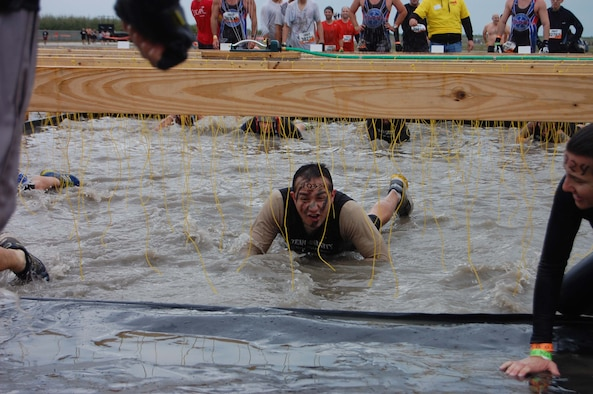 Tech. Sgt. Jesus Osuna, a member of the Air Force Technical Applications Center at Patrick AFB, Fla., makes his way through freezing water as 10,000 volts of electricity zap the participants during a Tough Mudder event that took place in Miami March 3, 2013.  Osuna was part of a 6-man team from the nuclear treaty monitoring center that completed the grueling 12-mile challenge.  (U.S. Air Force photo by Kevin Callan)
