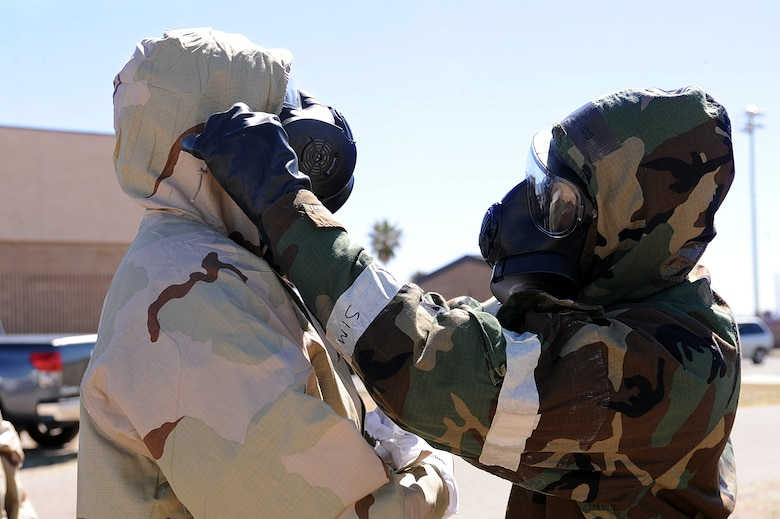 U.S. Air Force Airmen from the 355th Fighter Wing perform mission oriented protective posture equipment buddy checks during the operational readiness exercise on Davis-Monthan Air Force Base, Ariz., March 13, 2013. Airmen across the 355th Fighter Wing simulated many scenarios that consisted of self-aid and buddy care, and chemical, biological, radioactive nuclear explosive responses. (U.S. Air Force photo by Airman 1st Class Christine Griffiths/Released)