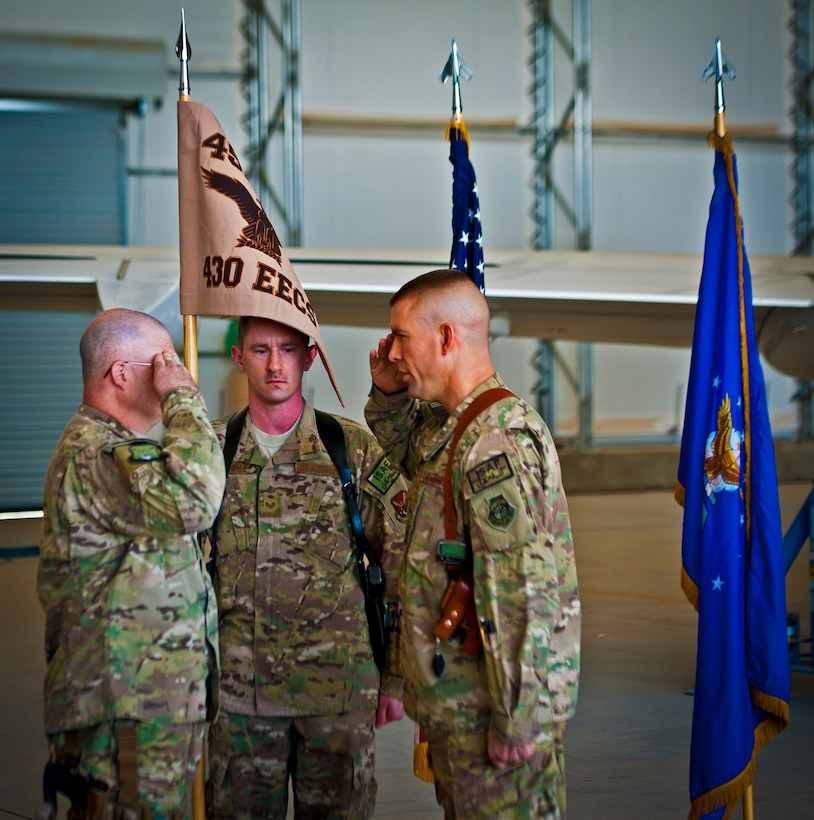 Chief Master Sgt. James Isom, 451st Expeditionary Operations Group superintendent, renders a salute to Col. Brook Leonard, 451st EOG commander, during an activation ceremony for the 430th Expeditionary Electronic Combat Squadron, at Kandahar Airfield, March 13, 2013. The unit, which flies the E-11A, was previously designated as the 451st Tactical Airborne Gateway. (U.S. Air Force photo/Senior Airman Scott Saldukas)