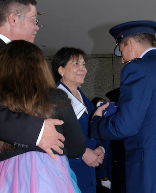 Tina Bush (center) receives a flag from Air Force Academy Superintendent Lt. Gen. Mike Gould during a memorial service March 16, 2013, for Chuck Bush, the first African American to graduate from the Academy. The couple was married for 48 years. Chuck Bush, who graduated from the Academy in 1963, died Nov. 5, 2012, at his home in Lolo, Mont. Also pictured are Michael Wills (left) and Grace Wills (lower left). (U.S. Air Force photo/Don Branum)