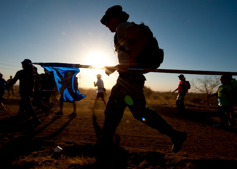 A participant in the 24th annual Bataan Memorial Death March runs with a guidon at White Sands Missile Range, N.M., March 17. More than 5,800 people who were from across the world participated in the 26.2-milememorial marathon to honor the 76,000 prisoners of war forced to endure marching nearly 80 miles under brutal conditions during World War II. The event included several military and civilian categories, both and without a 35-pound backpack. (U.S.  Air Force photo by Airman 1st Class Daniel E. Liddicoet/Released