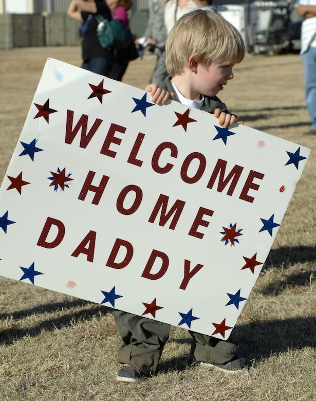 Teddy Arendsee, son of 1st Lt. Zacharee Arendsee, 40th Airlift Squadron, holds a welcome home sign while awaiting his father to de-board a C-130J March 15, 2013, at Dyess Air Force Base, Texas. For the first time in nearly a decade, the entire 317th Airlift Group fleet is back at their home station. (U.S. Air Force photo by Airman 1st Class Kylsee Wisseman/ Released)