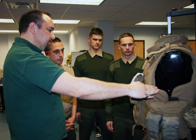 Carl Desantis (left), Gruntworks director, talks to a group of Marines about the improved modular tactical vest. The Marine Expeditionary Rifle Squad, or MERS, team worked with the program manager for Infantry Combat Equipment to develop and field the new fragmentation vest for the Marine Corps.