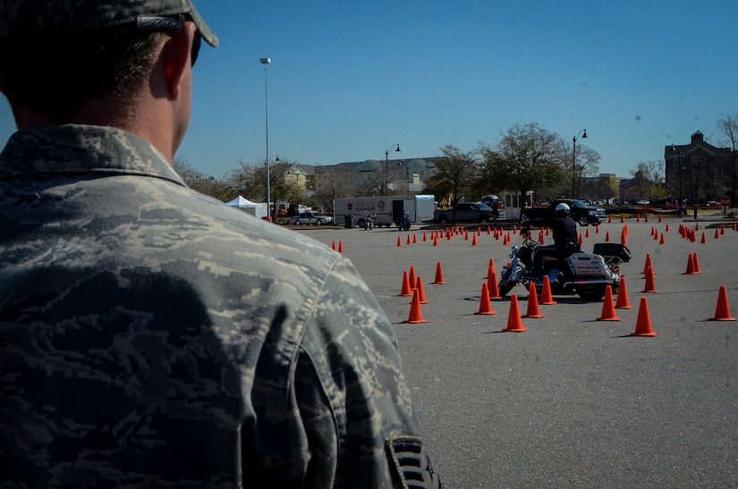 An Airman from Joint Base Charleston watches a deputy sheriff navigate through a motorcycle course during the Eighth Annual Palmetto Police Motorcycle Rodeo March 15, 2013 at the North Charleston Colisuem. More than 200 Airmen, Sailors, Soldiers, civilians and dependents participated in the 2013 Joint Base Charleston Motorcycle Safety Rodeo. More than 25 deputy sheriffs from South Carolina, Georgia and Florida completed obstacle courses designed to tests the limits of a motorcycle and the handling skills of the operators. (U.S. Air Force photo/Airman 1st Class Jared Trimarchi)