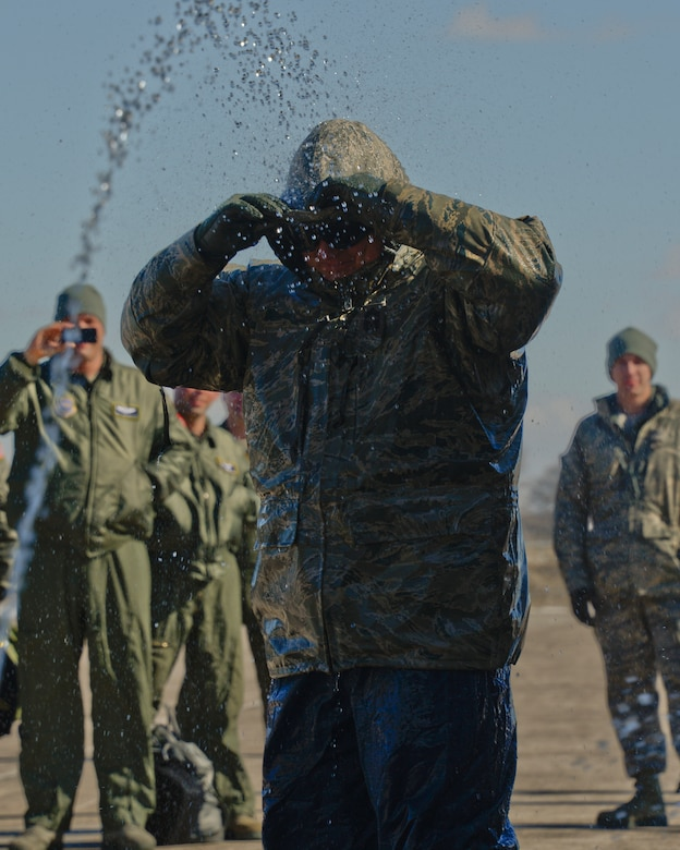 Airmen from the 133rd Airlift Wing spray a bridge of water over Chief Master Sgt. Jim Ricci, 109th Airlift Squadron in St. Paul, Minn., Mar. 16, 2013. Ricci is retiring from the military after over 35 years of service.  (U.S. Air Force photo by Staff Sgt. Amy M. Lovgren/Released)