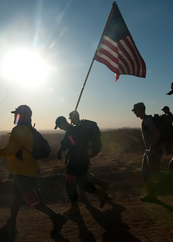 Participants in the 24th annual Bataan Memorial Death March carry an American flag after the start of the event at White Sands Missile Range, N.M., March 17. Over 5,800 people came to honor more than 76,000 Prisoners Of War/Missing In Action from Bataan and Corregidor during World War ll. The 26.2-mile course starts on WSMR, enters hilly terrain and finishes through sandy desert trails, with elevation ranging from 4,100-5,300 feet. This year 13 veterans from World War ll attended the event. (U.S. Air Force photo by Airman Leah Murray/Released)