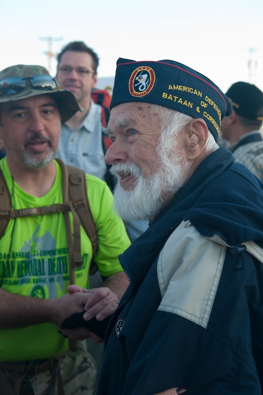 Oscar Leonard a World War ll survivor, stands at the start line and shakes hands with the participants in the 24th annual Bataan Memorial Death March at White Sands Missile Range, N.M., March 17. Over 5,800 people came to honor more than 76,000 Prisoners Of War/Missing In Action from Bataan and Corregidor during World War ll. The 26.2-mile course starts on WSMR, enters hilly terrain and finishes through sandy desert trails, with elevation ranging from 4,100-5,300 feet. This year 13 veterans from World War ll attended the event. (U.S. Air Force photo by Airman Leah Murray/Released)