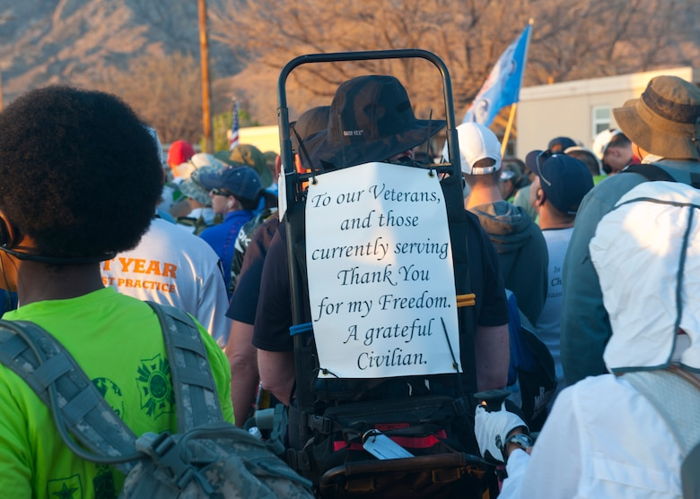 A participant in the 24th annual Bataan Memorial Death March shows his appreciation for veterans and active duty service members with a sign at White Sands Missile Range, N.M., March 17. Over 5,800 people came to honor more than 76,000 Prisoners Of War/Missing In Action from Bataan and Corregidor during World War ll. The 26.2-mile course starts on WSMR, enters hilly terrain and finishes through sandy desert trails, with elevation ranging from 4,100-5,300 feet. This year 13 veterans from World War ll attended the event. (U.S. Air Force photo by Airman Leah Murray/Released)